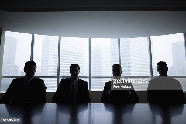 silhouette row of businessmen sitting in meeting room - schaduw stockfoto's en -beelden