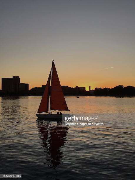 silhouette sailboat on sea against clear sky during sunset - norfolk virginia stock pictures, royalty-free photos & images
