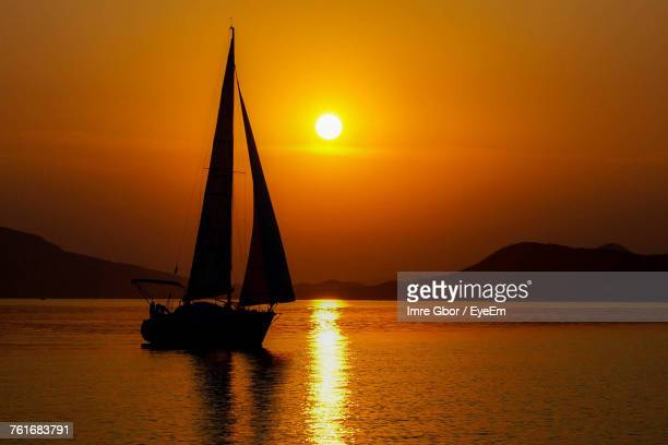 Silhouette Sailboat On Sea Against Orange Sky