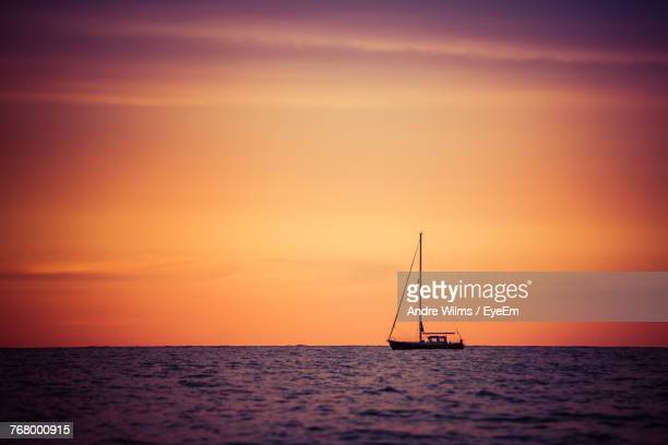 silhouette sailboat sailing on sea against sky during sunset - andre wilms eyeem stock-fotos und bilder