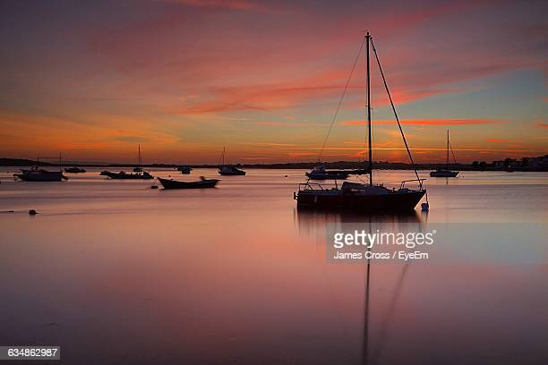 Silhouette Sailboats In Sea Against Orange Sky During Sunset