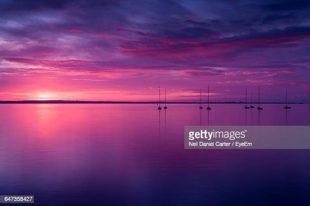 Silhouette Sailboats In Sea Against Purple Sky During Sunset