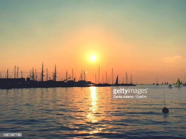 silhouette sailboats in sea against sky during sunset - adamo photos et images de collection