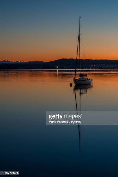 Silhouette Sailboats Moored In Lake Against Sky During Sunset