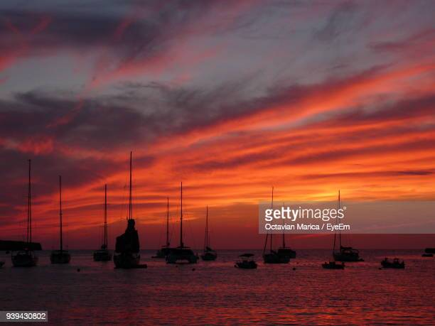 silhouette sailboats sailing on sea against orange sky - marica octavian stock photos and pictures