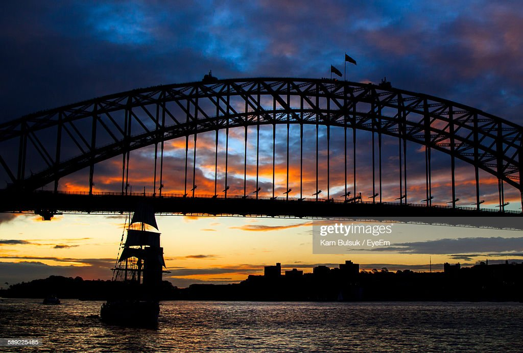 Silhouette Sailing Ship In Bay Of Water Against Sydney Harbor Bridge : Stock Photo