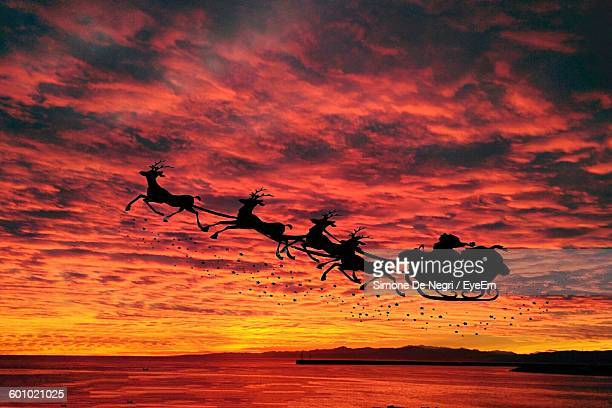 silhouette santa claus sled against orange sky during sunset - sleigh stock photos and pictures