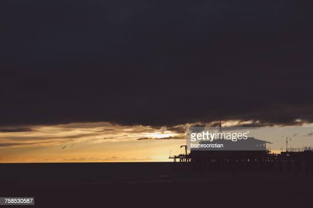 silhouette santa monica pier against cloudy sky during sunset - bortes foto e immagini stock