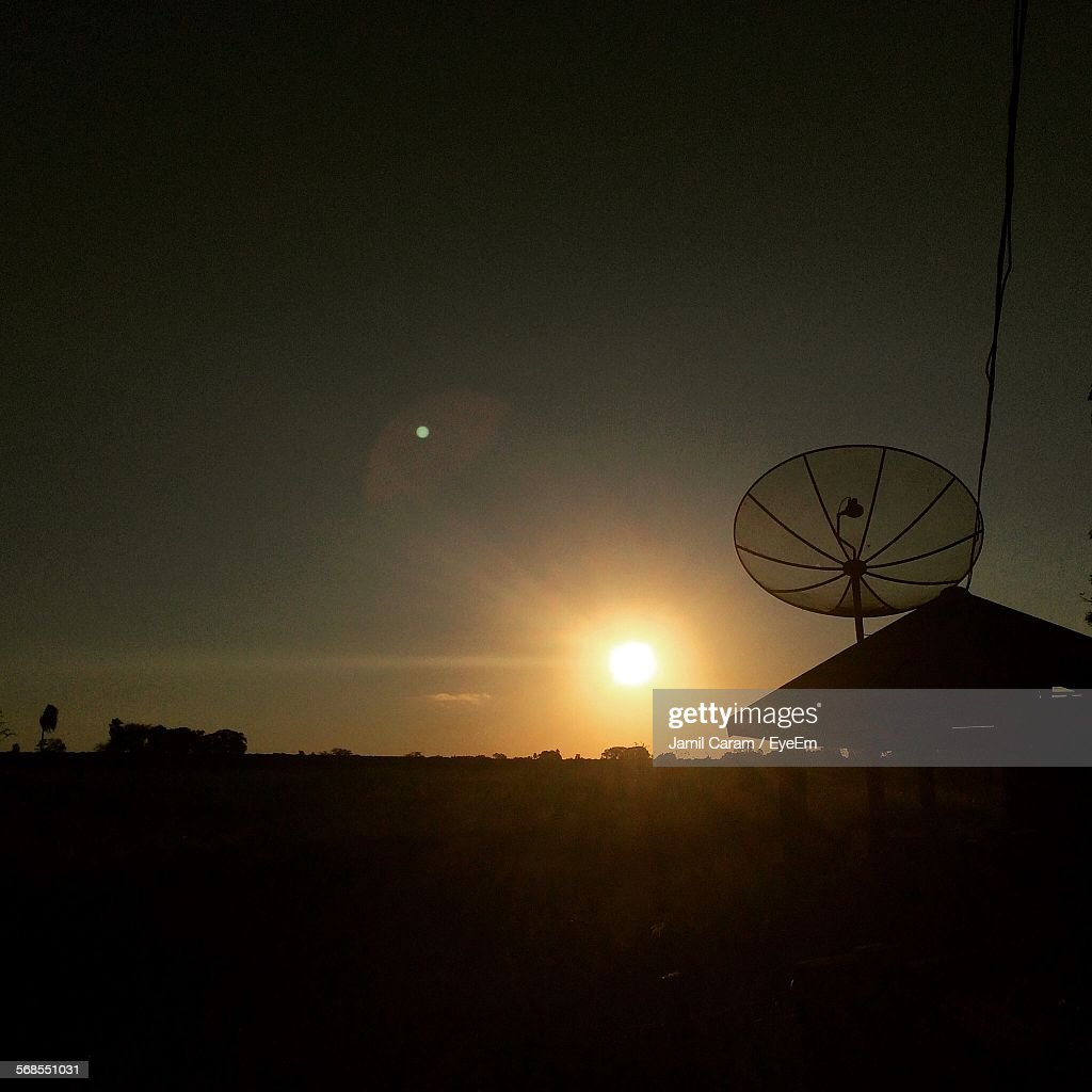 Silhouette Satellite Dish On Field During Sunset : Stock Photo