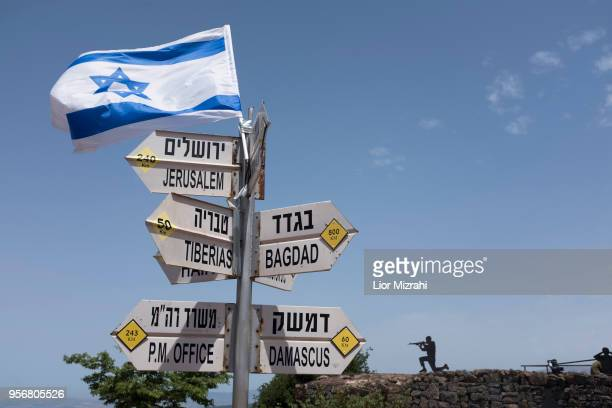 A silhouette sculpture of an Israeli soldier standing guard is seen next to a signs pointing out distance to different cities on Mount Bental next to...