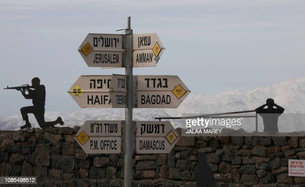 Silhouette sculptures of Israeli soldiers are pictured next to a sign for tourists showing the respective distances to Damascus and Baghdad from an...