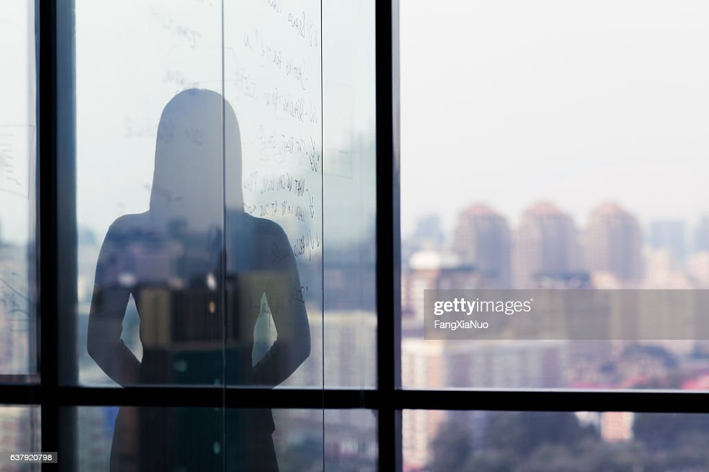 Silhouette shadow of woman looking at city from office : Stock Photo