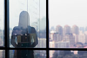Silhouette shadow of woman looking at city from office