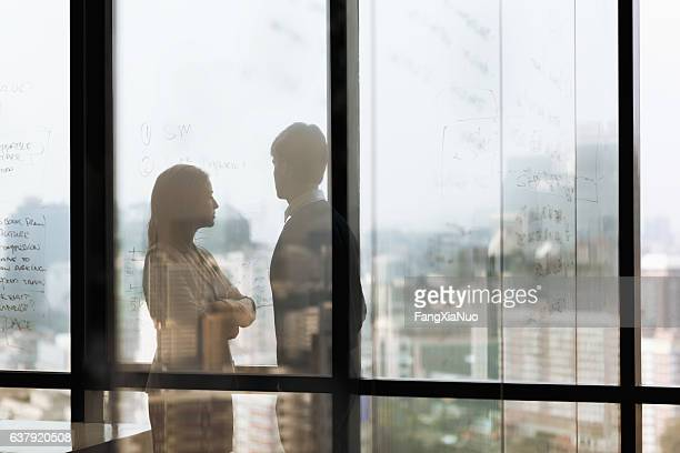 silhouette shadows of business people looking at city in office - 対立 ストックフォトと画像