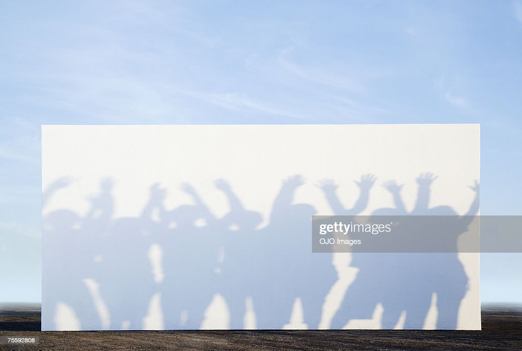 Silhouette shadows of people on a billboard : Stock Photo