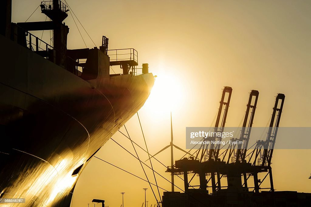 Silhouette Ship And Cranes At Harbor During Sunset : Stock Photo