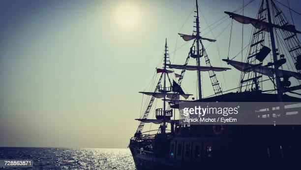 Silhouette Ship Sailing On Sea Against Clear Sky
