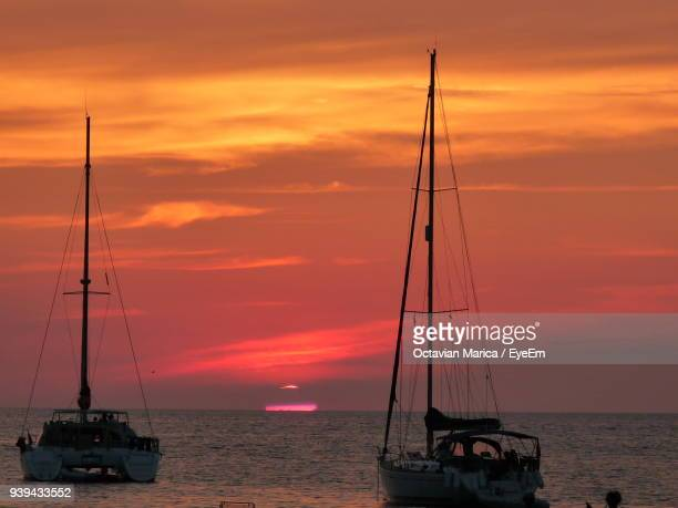 silhouette ship sailing on sea against orange sky - marica octavian stock photos and pictures
