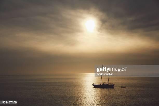 silhouette ship sailing on sea against sky during sunset - bortes fotografías e imágenes de stock
