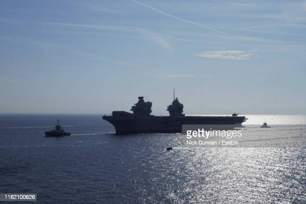 silhouette ship sailing on sea against sky - british military stock pictures, royalty-free photos & images