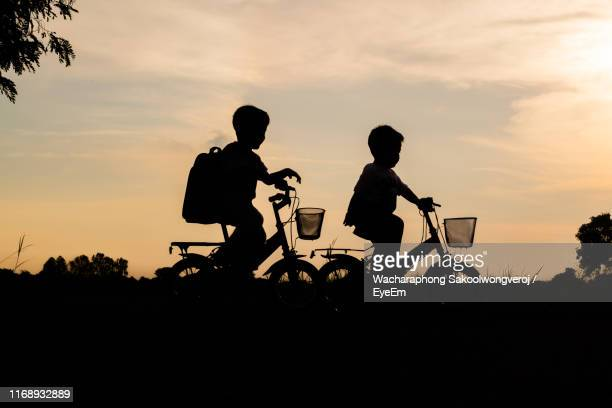 silhouette siblings riding bicycles on land against sky during sunset - hermano fotografías e imágenes de stock