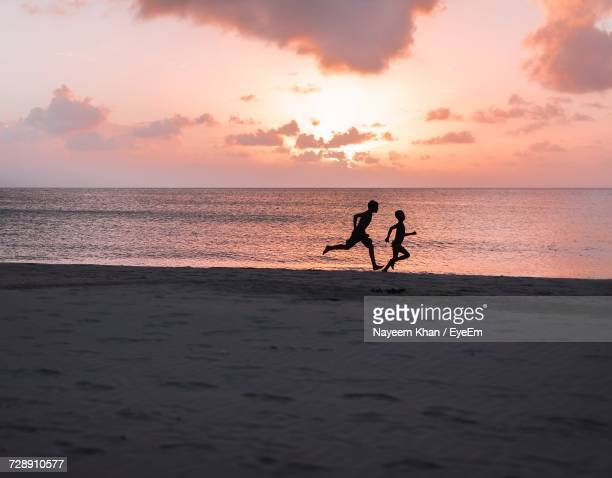 Silhouette Siblings Running At Beach During Sunset