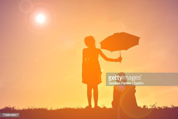 Silhouette Sister Holding Umbrella While Brother Sitting On Field Against Sky During Sunset