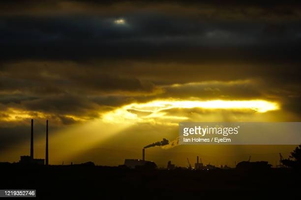 silhouette smoke emitting from chimney against sky during sunset - factory stock pictures, royalty-free photos & images
