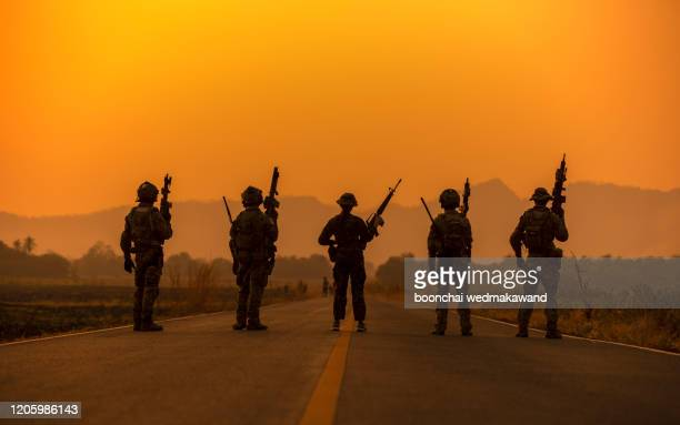 silhouette soldiers on the sunset sky background - army stock pictures, royalty-free photos & images