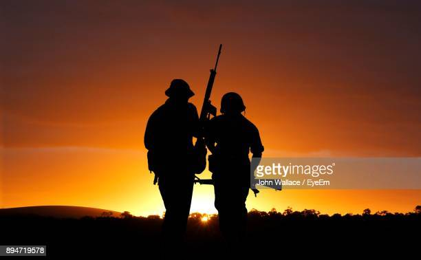 Silhouette Soldiers Standing Against Orange Sky During Sunset