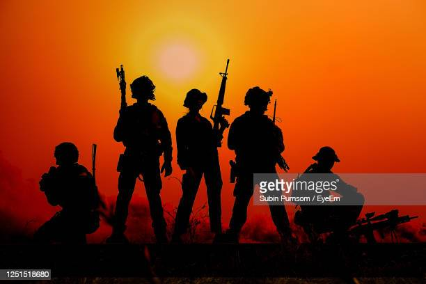 silhouette soldires on land against sky during sunset - afghanistan stock pictures, royalty-free photos & images