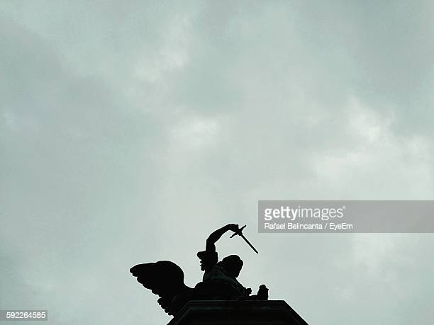 Silhouette Statue Of Archangel Michael Against Cloudy Sky
