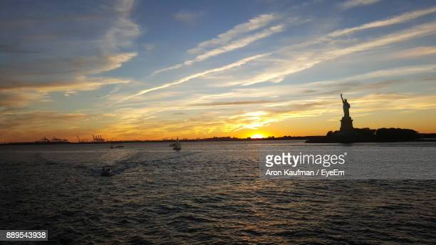 Silhouette Statue Of Liberty By River During Sunset