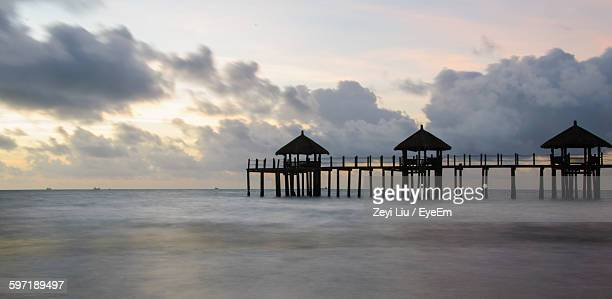 silhouette stilt house amidst sea against sky during sunset - liu he stock pictures, royalty-free photos & images