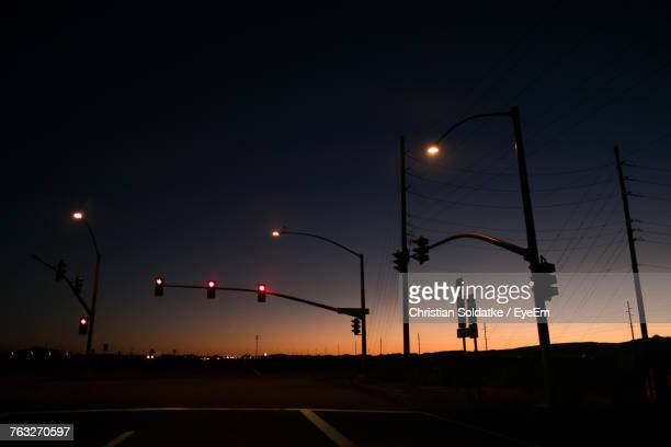 silhouette stoplights against sky during sunset - christian soldatke stock pictures, royalty-free photos & images