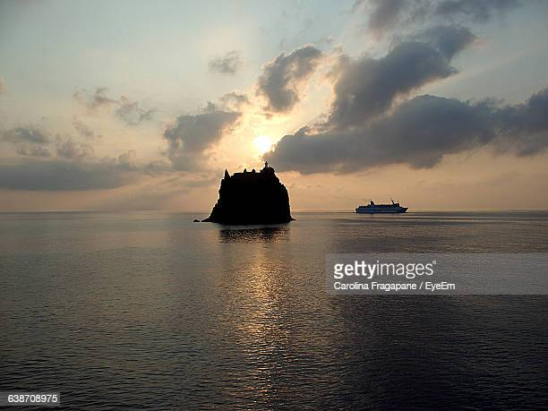 silhouette strombolicchio and sea against sky during sunset - carolina fragapane stock pictures, royalty-free photos & images