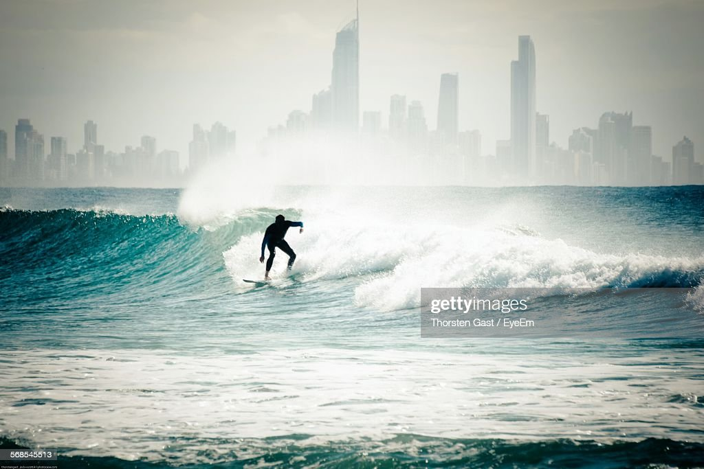 Silhouette Surfer Surfing In Sea In Front Of Cityscape : Stock Photo