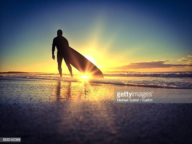 Silhouette Surfer With Surfboard Walking On Beach Against Sky During Sunset