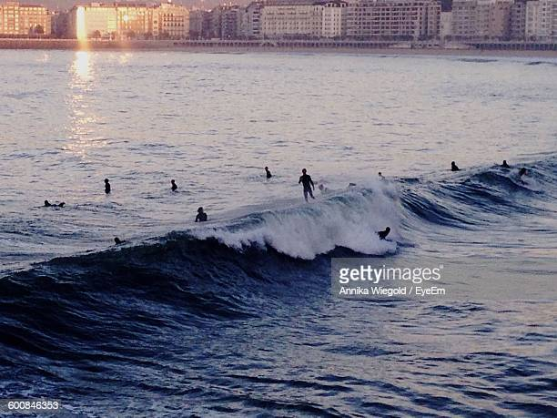 Silhouette Surfers Surfing On Sea Against Building During Sunset