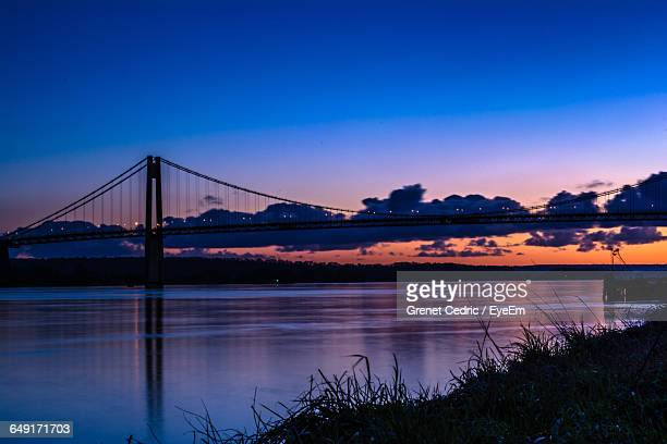 Silhouette Tancarville Bridge Over River Against Sky During Sunset
