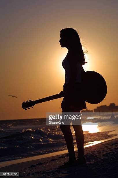 Silhouette Teen Girl holding Guitar at Beach during Sunset