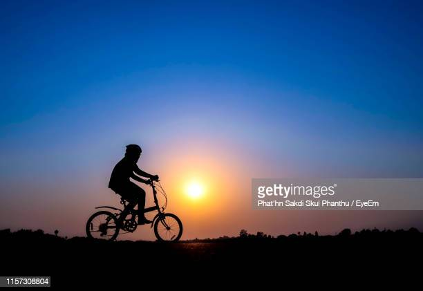 silhouette teenage boy riding bicycle on field against blue sky during sunset - one teenage boy only stock pictures, royalty-free photos & images
