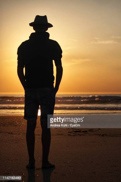 silhouette teenage boy standing at beach against sky during sunset - one teenage boy only stock pictures, royalty-free photos & images