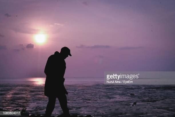 Silhouette Teenage Boy Walking At Beach Against Sky During Sunset