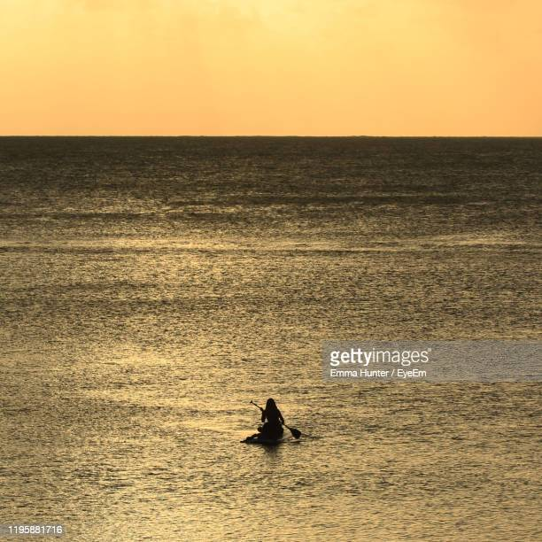 silhouette teenage girl paddleboarding on sea against clear sky during sunset - emma hunter eye em stock photos and pictures