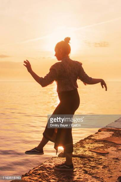 Silhouette Teenage Girl Standing On Pier During Sunset