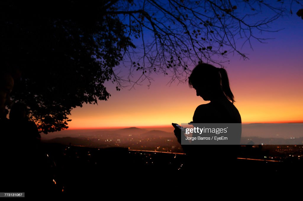 Silhouette Teenage Girl Using Smart Phone Against Sky During Sunset : Photo