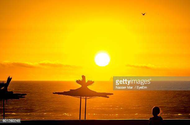 silhouette thatched roofs at beach against sky during sunset - agadir photos et images de collection