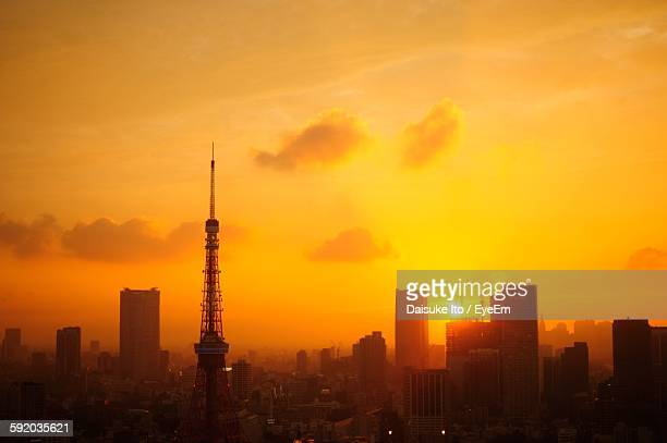 Silhouette Tokyo Tower Against Buildings At Sunset