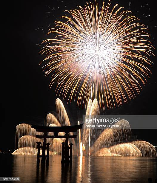 silhouette torii gate in lake against firework display at night - hiroshima imagens e fotografias de stock